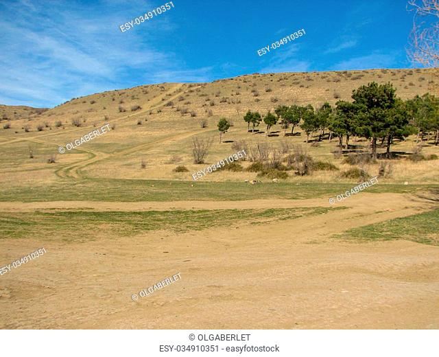 Hill covered of yellow grass under clear blue sky in Georgia Nutsubidze Tbilisi, Lisi lake great wave of water in the hills stones dry grass and cane