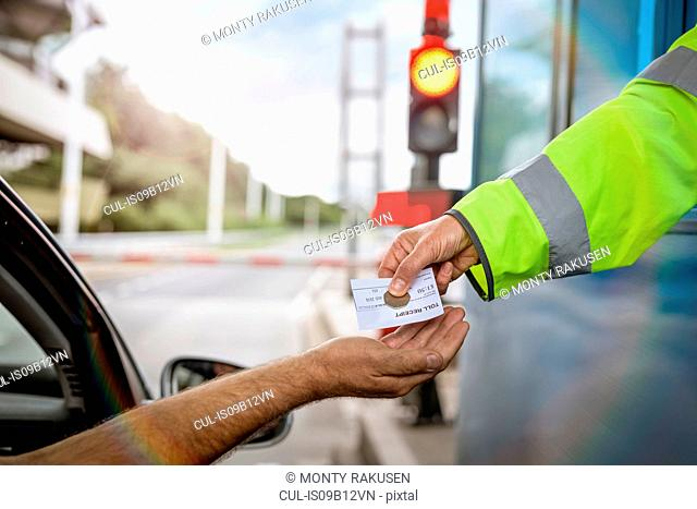 Driver in car paying toll booth at bridge, close up