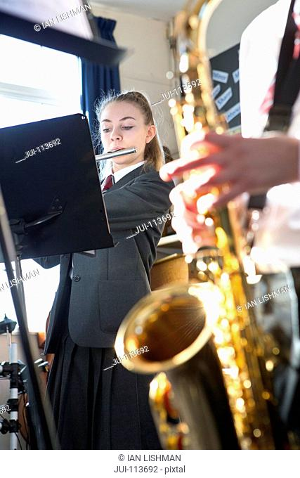 High school students playing saxophone and flute at music stand in music class