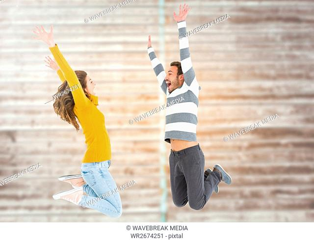 Composite image of couple jumping against bricks wall