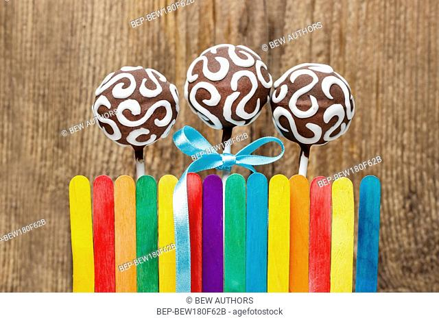 Chocolate cake pops and colorful rainbow fence on wooden background