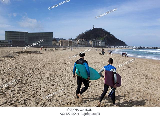 Two surfers in wetsuits walking towards the waves with the two glass cubes of the Kursaal, cultural centre, next to the Rio Urumea and the Zurriola beach in the...