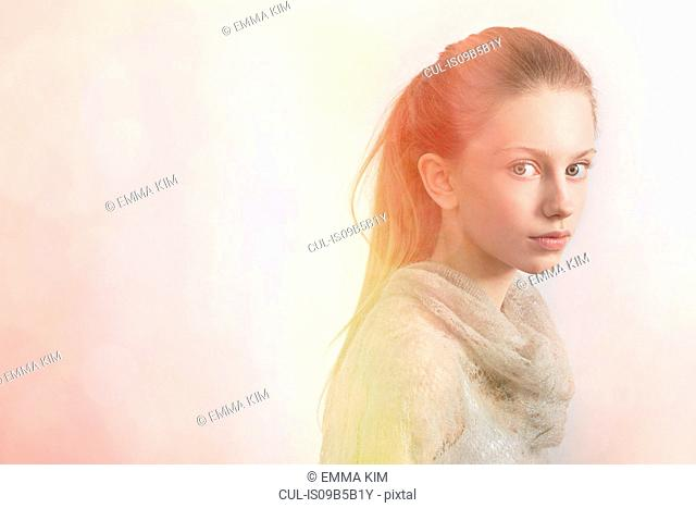 Portrait of girl against pale background
