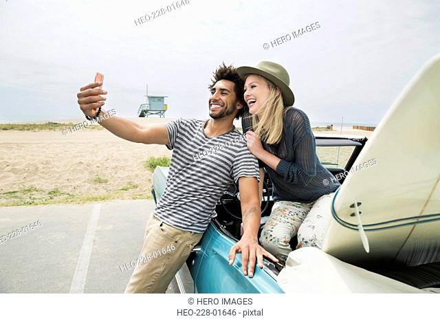 Young couple convertible surfboard taking selfie at beach