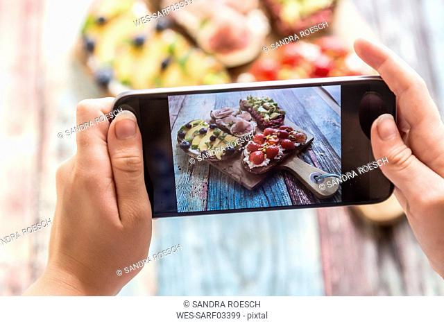 Girl photographing with her smartphone, various sandwiches on chopping board