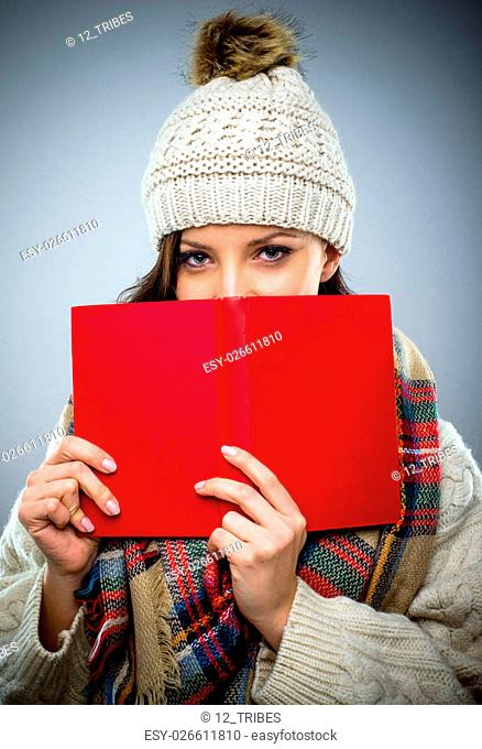 Coy young woman in a woolly winter cap reading a red hardcover book holding it to her face as she peers over the top at the camera