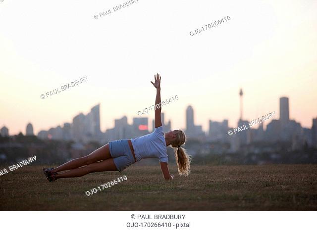 Woman practicing yoga in urban park