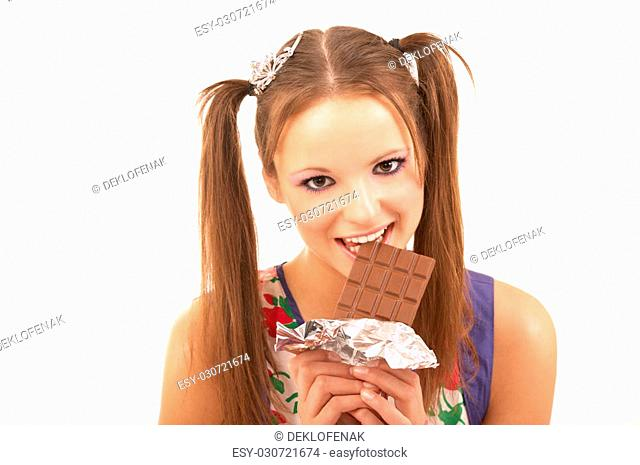 The young beautiful girl bites off a slice of chocolate