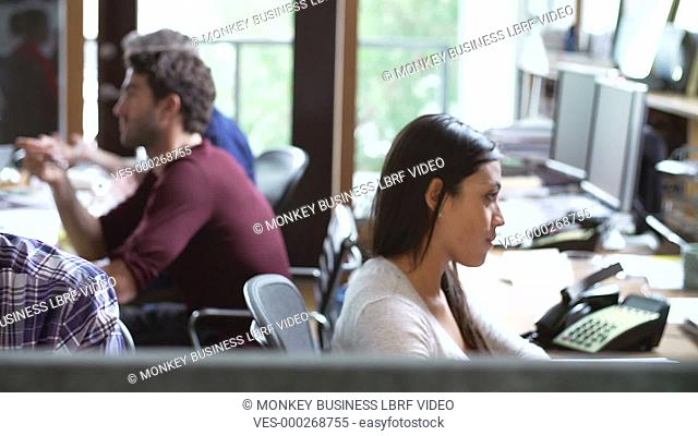 Camera tracks across office to show architect working at desk whilst colleagues have meeting in background.Shot on Sony FS700 in PAL format at a frame rate of...