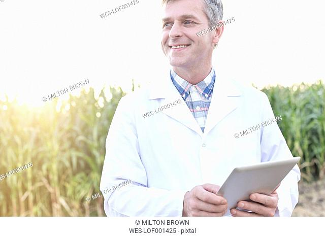 Smiling scientist with digital tablet at field