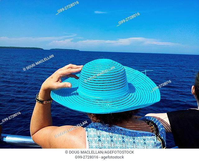 A woman holds on to her large blue hat during a boat cruise of Fathom Five National Marine Park on Georgian Bay, Ontario, Canada