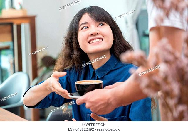 Barista served hot coffee to customer with smiling face at counter bar in cafe restaurant,coffee shop business owner concept,Service mind waitress