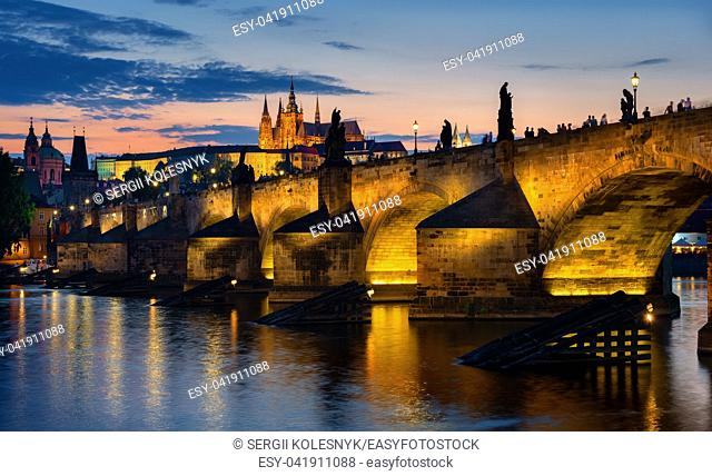 Sunset over illuminated Charles bridge in Prague