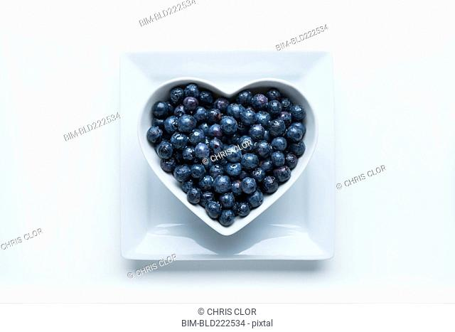 Blueberries in heart-shape bowl on white background