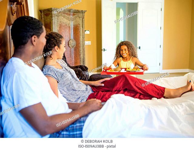 Girl serving parents breakfast in bed smiling