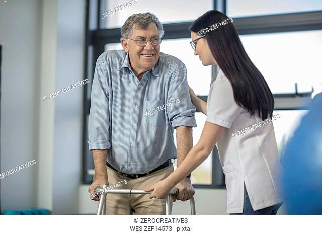 Nurse helping senior patient with walking frame