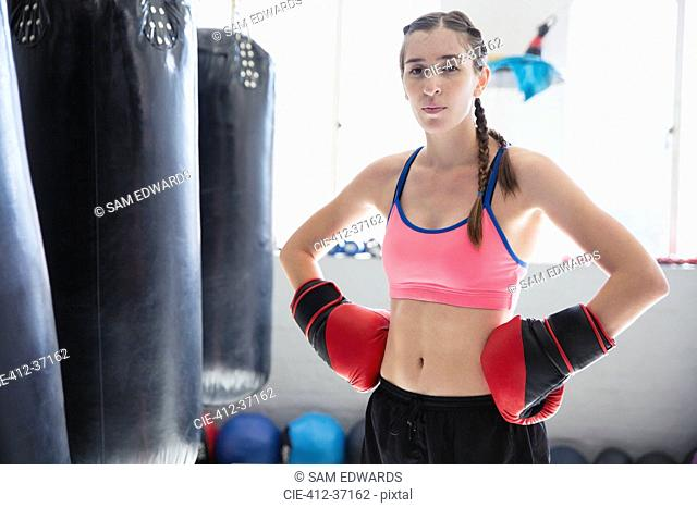 Portrait determined, tough young female boxer wearing boxing gloves with hands on hips at punching bags