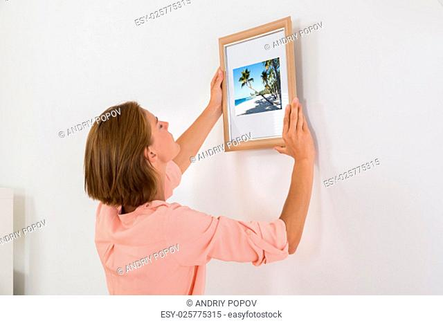 Young Woman Putting Photo Frame On White Wall