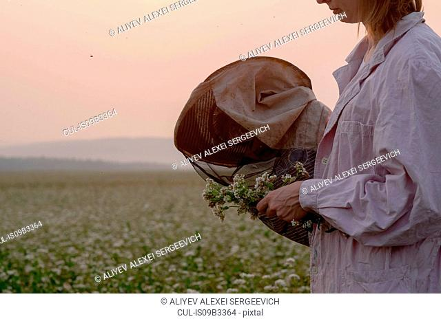Cropped shot of female beekeeper inspecting plant in flower field, Ural, Russia