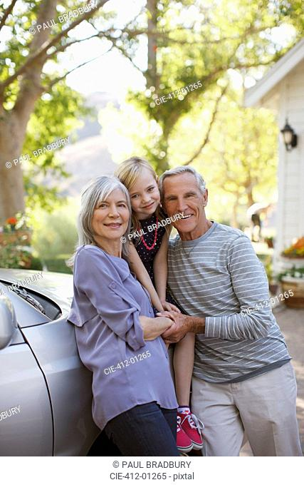 Older couple and granddaughter leaning on car