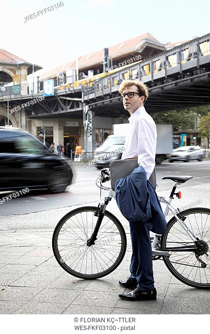 Germany, Berlin, portrait of businessman with bicycle and laptop bag standing on pavement