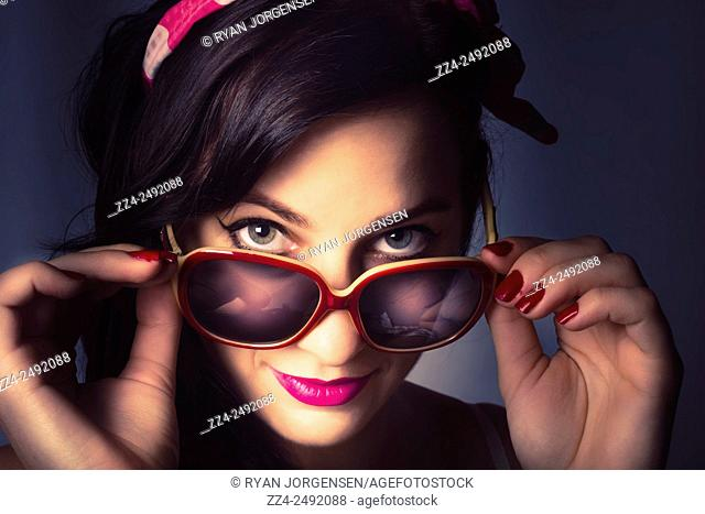 Vintage close up portrait of a beautiful model in pin-up styling wearing fashionable retro sunglasses. Cosmetics and manicures concept