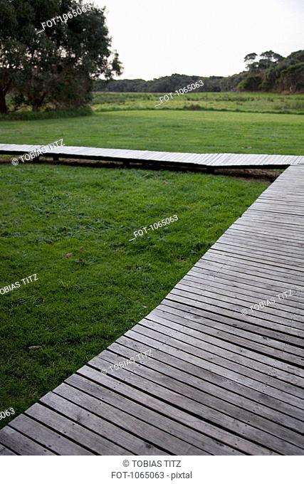 A wooden footbridge over grass in a remote location