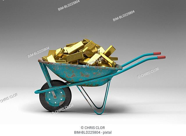 Rusty wheelbarrow full of gold bars