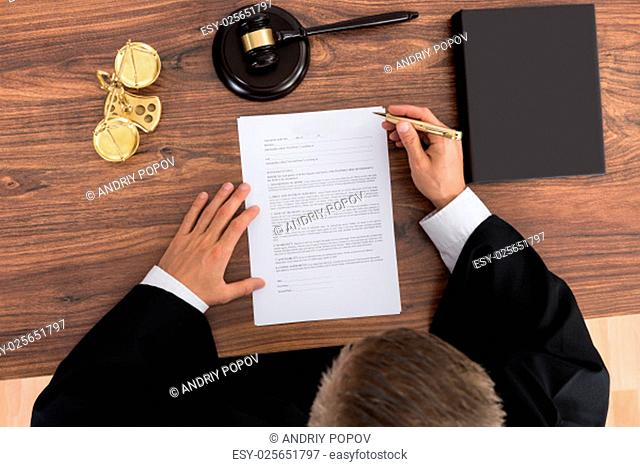 Close-up Of Male Judge Reading Paper In Courtroom