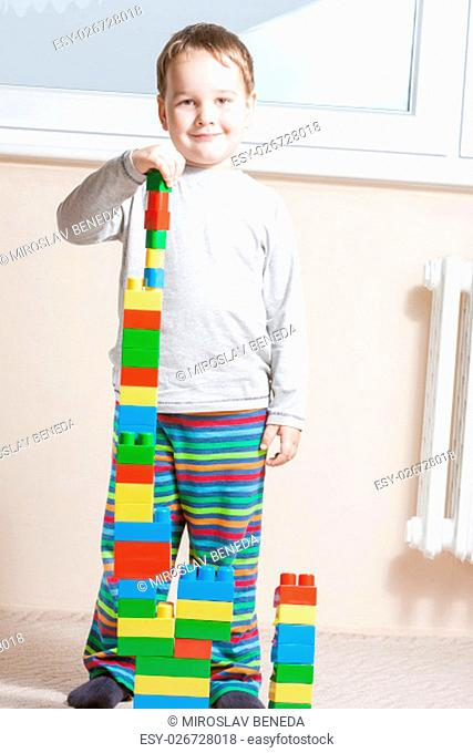 standing and smiling boy with built stack of colored cubes