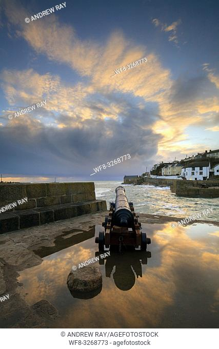 One of the Canon's at the entrance to the harbour at Porthleven on Cornwall's Lizard Peninsular, reflected in a large pool of water at sunset in February