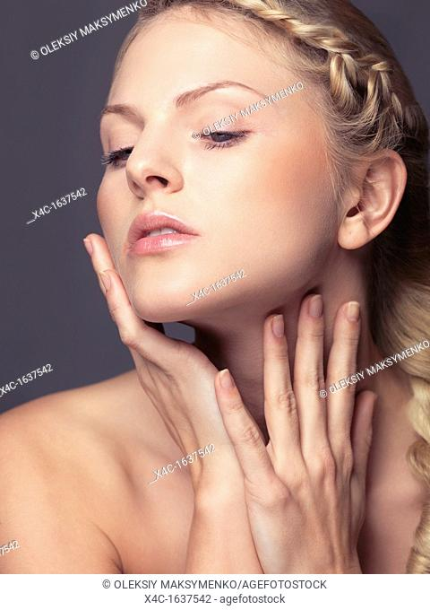 Beauty portrait of a young woman touching soft skin on her face and neck