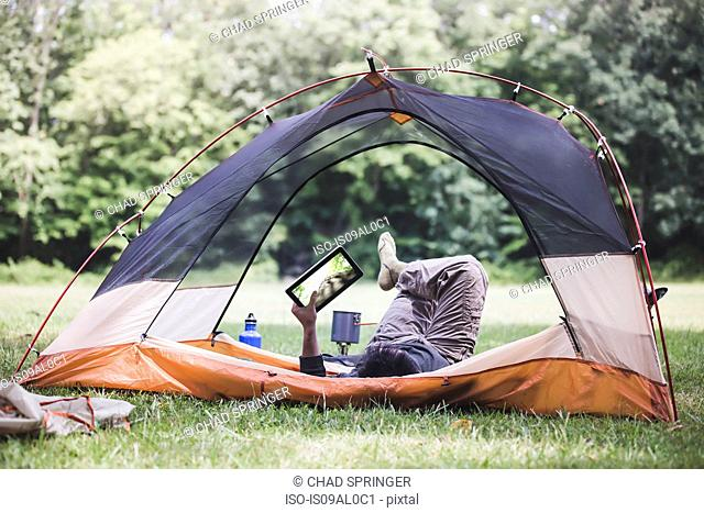 Mature man lying in tent using digital tablet