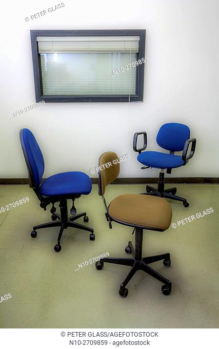 Three office chairs next to a window with blinds
