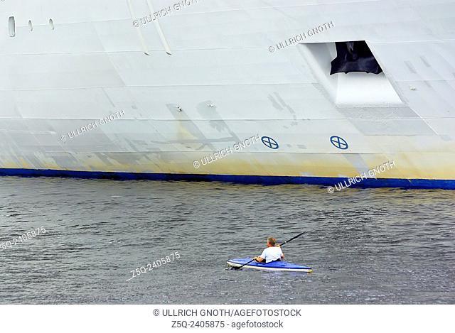A small kayak overtakes a big ocean liner