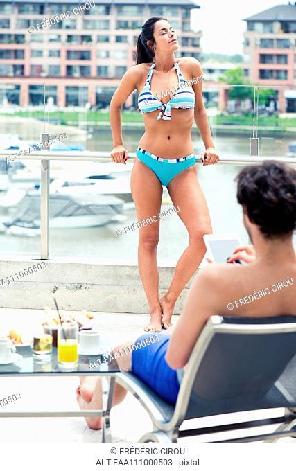 Woman sunbathing, man relaxing by pool using digital tablet