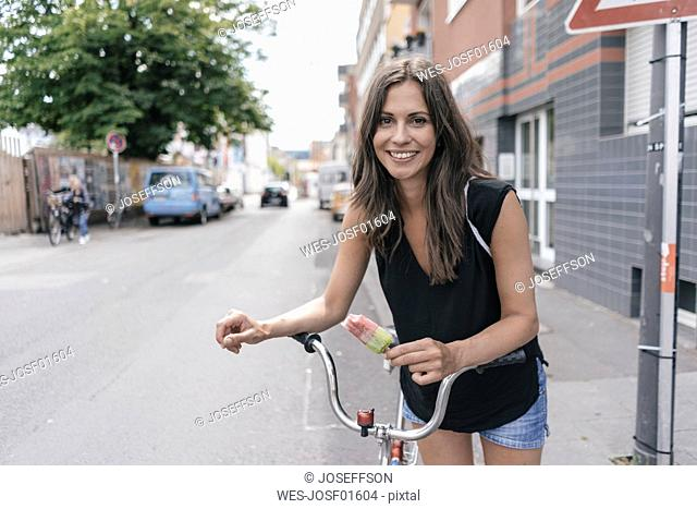 Smiling woman with ice lolly and bicycle