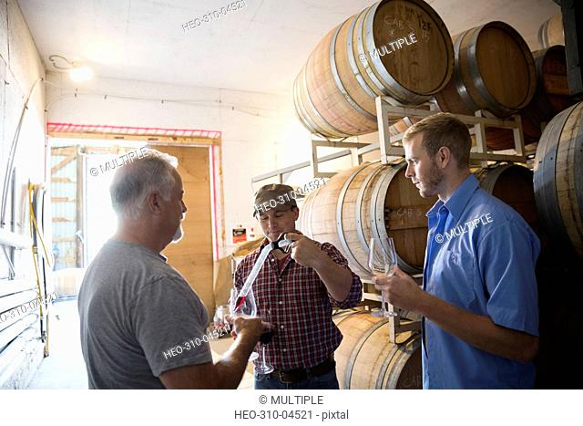 Male vintners checking and tasting wine in winery barrel room