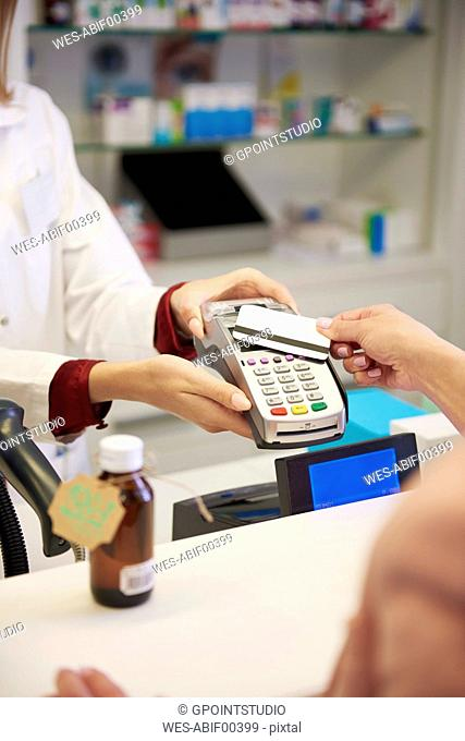 Customer paying cashless with credit card in a pharmacy