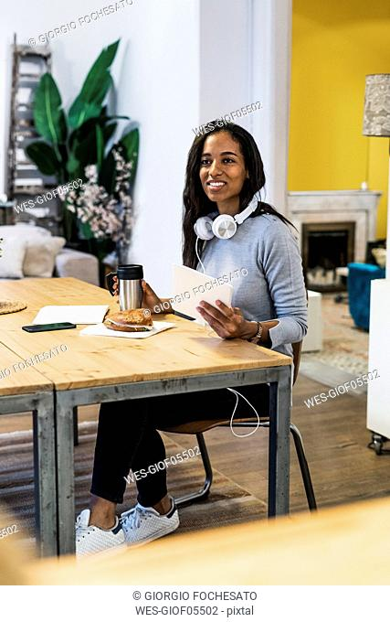 Smiling woman with tablet sitting at table