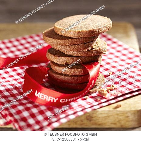 A stack of gingerbread biscuits with a ribbon for Christmas