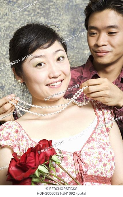 Young man putting a necklace around a young woman's neck
