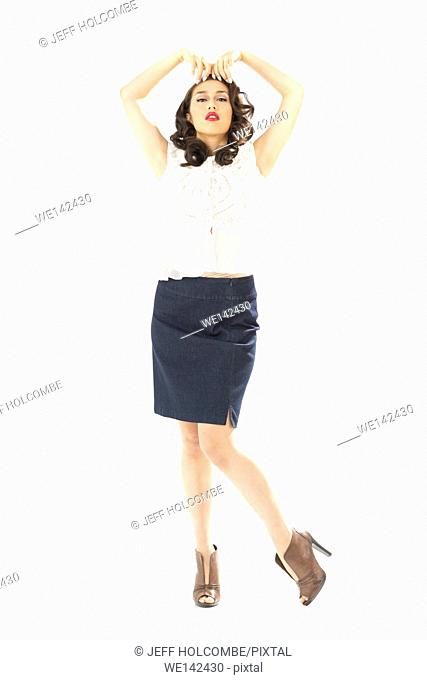 Beautiful young woman in white blouse and blue denim skirt, full length in brown heels, hands on top of forehead, facing forward