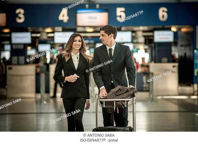 Businesspeople in airport with luggage trolley