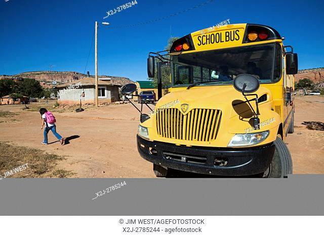 Thoreau, New Mexico - A Navajo girl runs home after being dropped off by a school bus from St. Bonaventure Indian School, a Catholic school on the Navajo Nation
