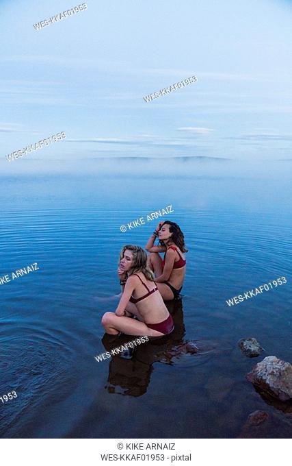 Two young women wearing bikinis, sitting on a stone in a lake
