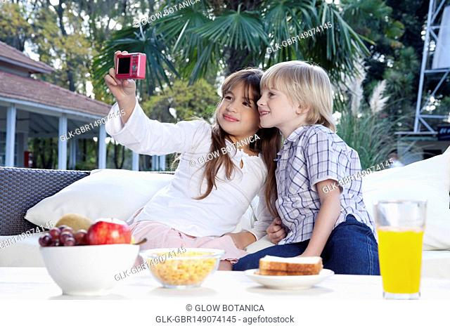 Girl taking a picture of herself and her brother with a digital camera