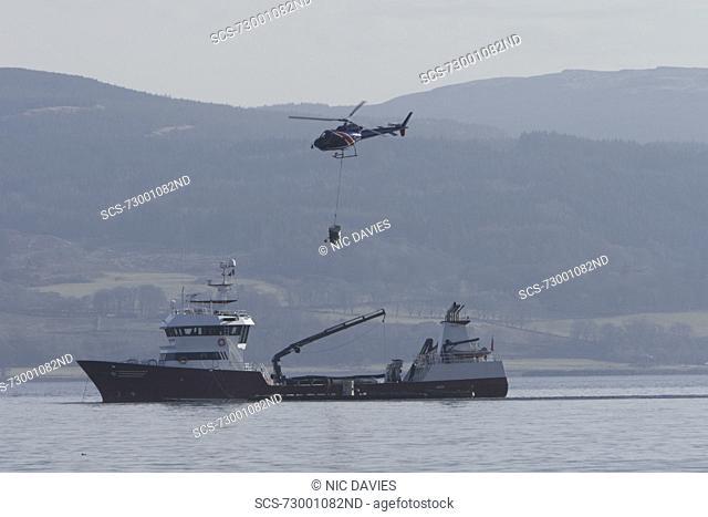 Helicopter supplying salmon farm Hebrides, UK