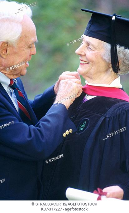 Senior woman wearing graduation cap and gown being congratulated by her husband on receiving college degree