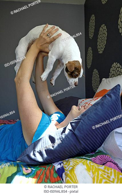 Woman lying on bed holding up dog